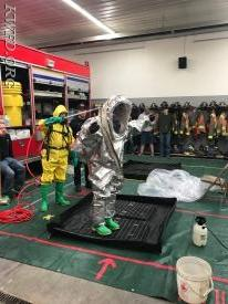 Ben Pancratz wearing the Level A Hazmat Suit (silver) as Todd Latham (yellow level B suit) demonstrates decontamination.